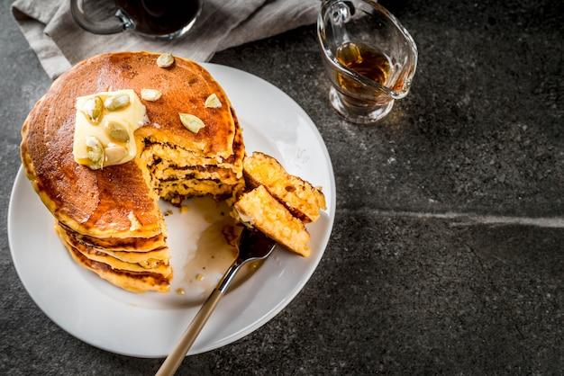Comida tradicional otoñal. pila de panqueques de calabaza con mantequilla, semillas de calabaza y jarabe de arce. con una taza de cafe. sobre una mesa de piedra negra. copyspace