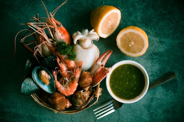 Comida de vapor servida concepto de buffet de mariscos. camarones frescos langostinos calamares mejillones manchados babilonia marisco cangrejo y salsa de mariscos limón en placa piedra negra
