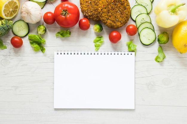 Comida vegana junto al cuaderno vacío en la mesa de madera blanca