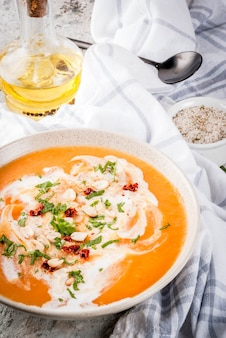 Comida vegana de moda, sopa de desintoxicación de batata con leche de coco, tomates secos, maní y hierbas, en el espacio de copia de la mesa de piedra gris