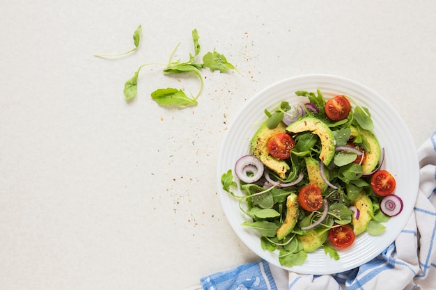 Comida vegana en un plato con fondo blanco.