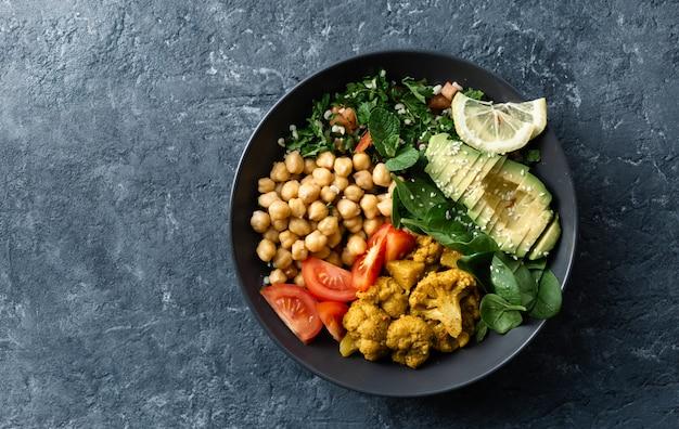 Comida vegetariana saludable con garbanzos, tomate, aguacate y espinacas