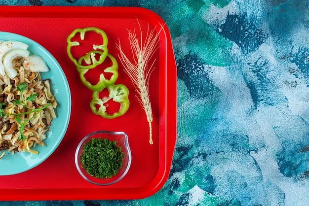 Comida para uno con verduras en rodajas en la bandeja, en la mesa azul.