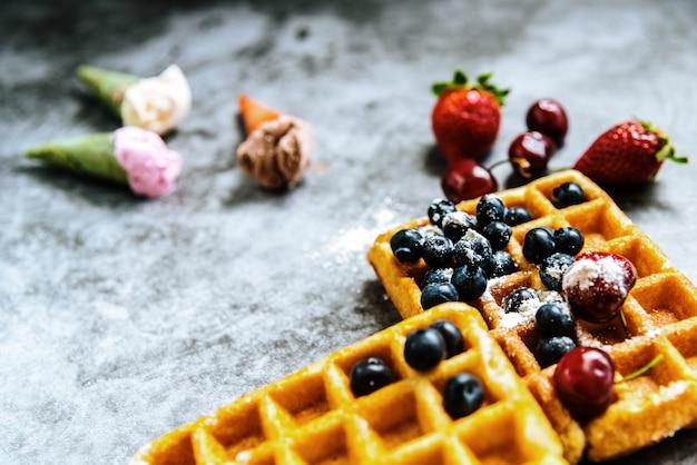 Comidas sabrosas y dulces con frutas rojas y waffles