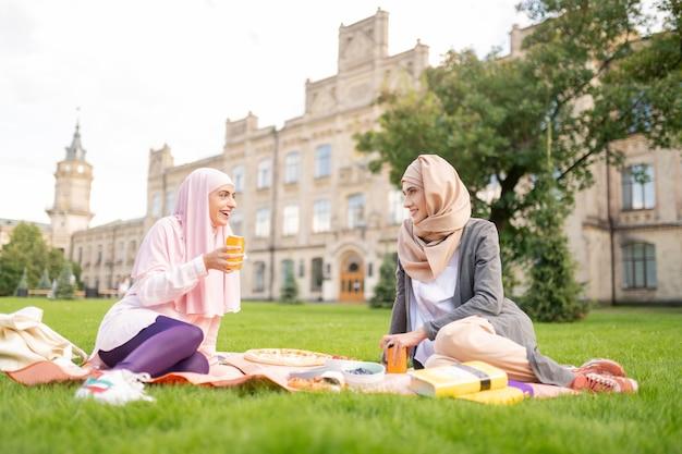 Comiendo y bebiendo. estudiantes musulmanes comiendo y bebiendo mientras están sentados en el césped cerca de la universidad