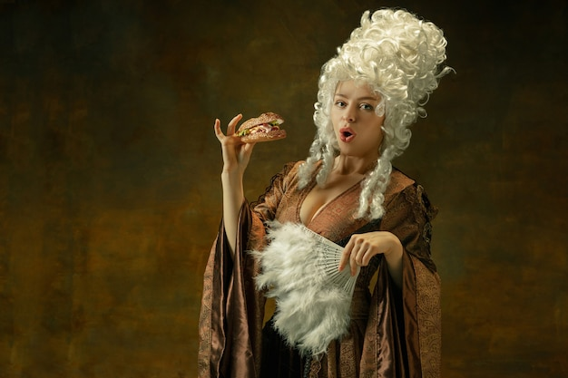 Comiendo hamburguesa encantado. retrato de mujer joven medieval en ropa vintage marrón sobre fondo oscuro. modelo femenino como duquesa, persona real. concepto de comparación de épocas, moderno, moda, belleza.