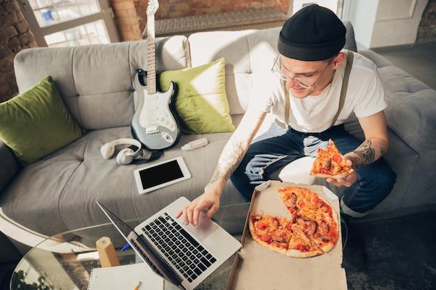 Comiendo pizza. hombre estudiando en casa durante cursos en línea, escuela inteligente.