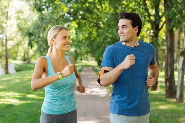 Comienzo del día. alegre pareja positiva sonriendo el uno al otro mientras trota por la mañana juntos