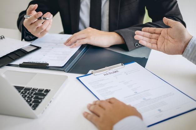 Comité o reclutador que mantiene leyendo un currículum durante el coloquio sobre su perfil de candidato