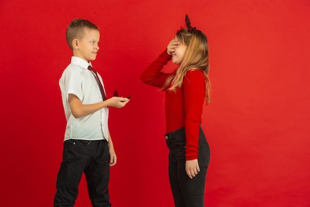 Como un adulto. celebración del día de san valentín, felices, lindos niños caucásicos aislados sobre fondo rojo de estudio. concepto de emociones humanas, expresión facial, amor, relaciones, vacaciones románticas.
