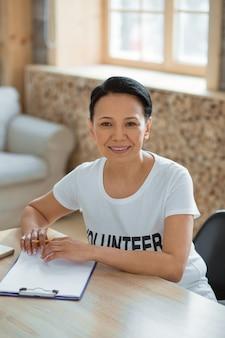 Cómo ayudar. vista superior de feliz agradable voluntario sentado en la mesa mientras sostiene el lápiz y mirando a la cámara