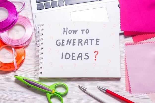¿cómo generar ideas? mensaje en el cuaderno sobre tela textil y cinta en la mesa de trabajo de modista