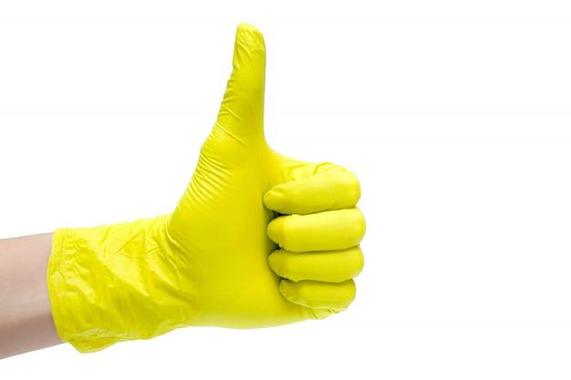 Como icono de signo hecho de guantes médicos amarillos. dedo de la mano hasta el símbolo.