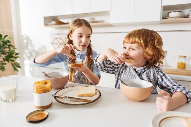 Como mamá. encantadora señorita untando un poco de mantequilla de maní en un trozo de pan mientras su hermano lo prueba y se ve muy complacido
