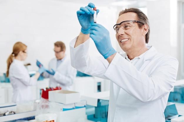 Como este proceso. varón sonriente con gafas protectoras levantando las manos mientras examina el tubo de ensayo