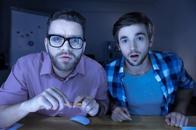 Cómo puede ser. hombres agradables sorprendidos sentados juntos y mirando la pantalla de la computadora mientras muestran su asombro