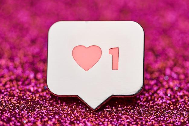 Como símbolo del corazón. como botón de signo, símbolo con corazón y un dígito. mercadeo en redes sociales. fondo de chispas de brillo rosa.