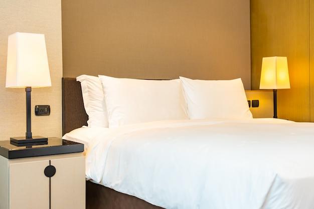Cómoda almohada blanca y manta en la cama con lámpara de luz