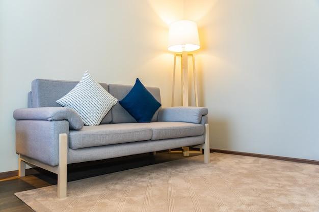 Cómoda almohada en la decoración del sofá con luz interior de la lámpara