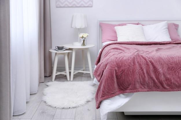Cómoda cama con colcha y almohadas de color rosa suave en una habitación moderna y luminosa
