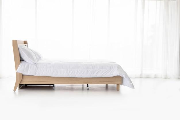 Cómoda cama para dormir relajarse en el dormitorio telón de fondo de cortinas blancas