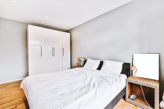 Cómoda cama con edredón arrugado ubicado cerca de las mesitas de noche con lámparas y cuadros contra la ventana con cortinas en el dormitorio iluminado