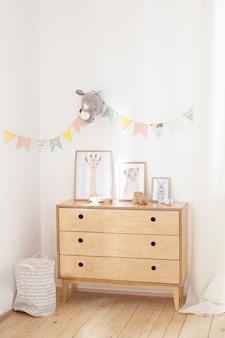 Cómoda de madera, carteles y juguetes ecológicos contra una pared blanca con banderas multicolores. el concepto de un acogedor interior y inauguración de la casa. un cofre con ropa y un cesto de la ropa en una pared blanca.