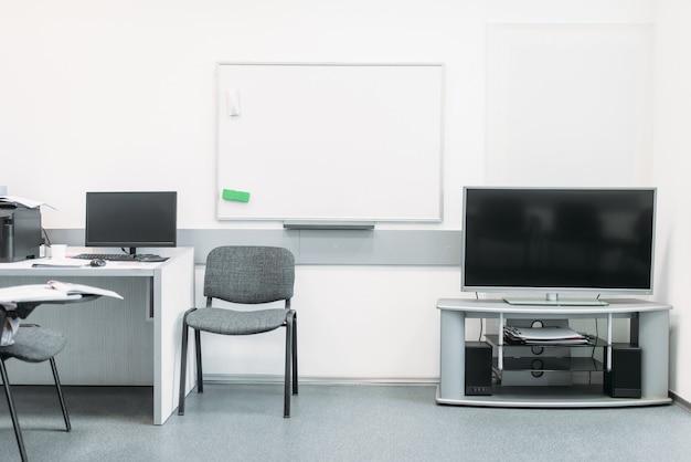 Cómoda oficina de negocios en tonos blancos con equipamiento moderno