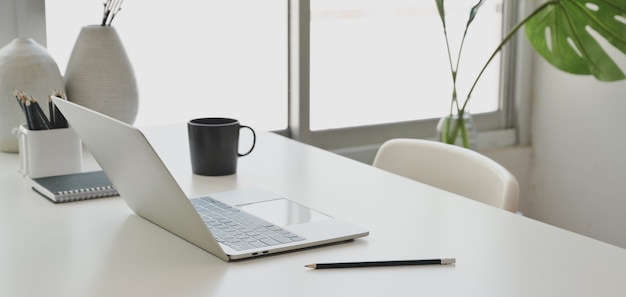 Cómoda sala de oficina con computadora portátil y útiles de oficina en mesa de madera blanca