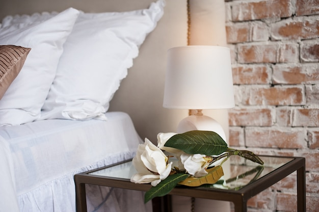 Cómoda y serena mesita de noche con lámpara junto a la cama