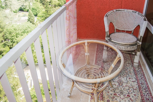 Una cómoda zona de estar en el balcón con una silla de mimbre de ratán, una mesa de vidrio transparente y una alfombra, un concepto de recreación en el hogar.
