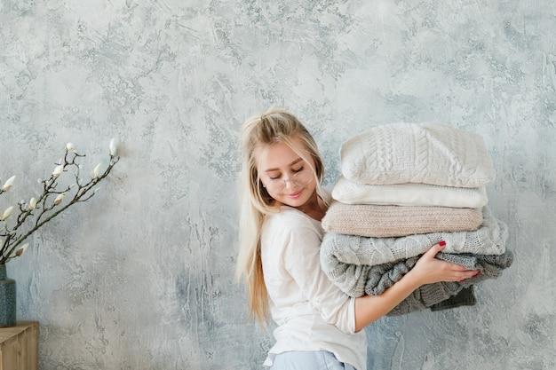 Comodidad del dormitorio de invierno. señora feliz con pila de almohada y manta de punto caliente.