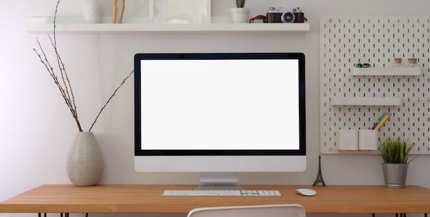 Cómodo espacio de trabajo con computadora de escritorio de pantalla en blanco y suministros de oficina