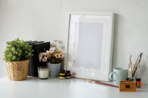 Cómodo espacio de trabajo con marco de póster de maqueta y espacio de copia.