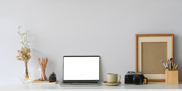 Cómodo espacio de trabajo rodeado de computadora portátil con pantalla blanca,