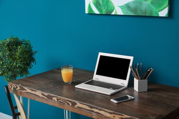 Cómodo lugar de trabajo en casa con computadora portátil en el escritorio