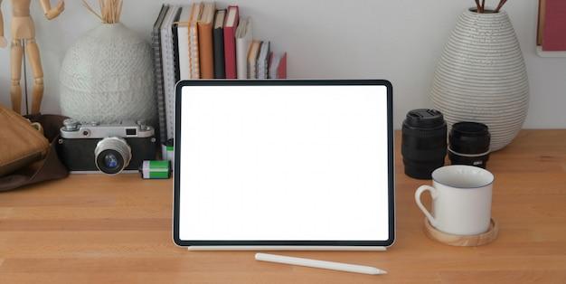 Cómodo lugar de trabajo de fotógrafo con tableta digital de pantalla en blanco y suministros de oficina