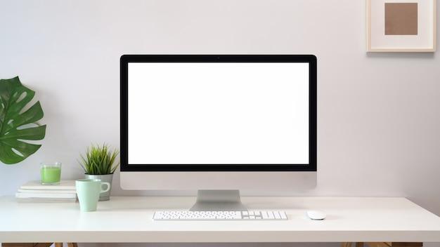 Cómodo lugar de trabajo con ordenador de pantalla en blanco.