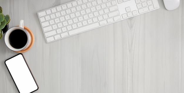 Cómodo lugar de trabajo con pantalla en blanco de teléfono inteligente, material de oficina y espacio de copia