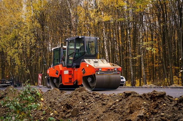 Compactador de rodillos de vibración en tándem trabajando en pavimento de asfalto, enfoque selectivo en la reparación de carreteras.
