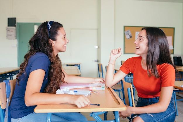 Compañeras de clase charlando y riéndose