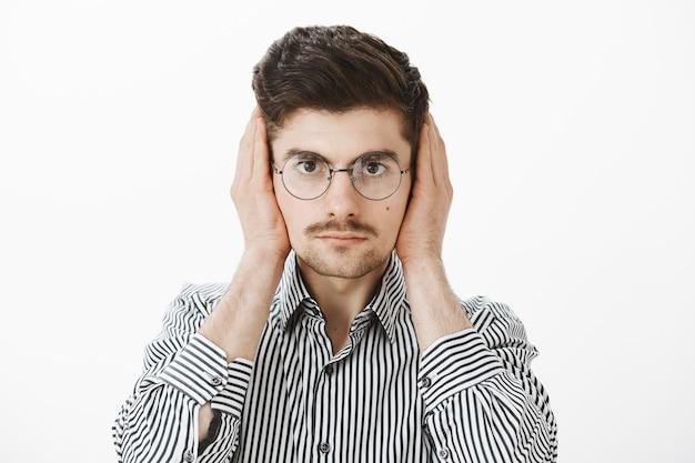 Compañero de cuarto ruidoso distrae al chico del trabajo independiente. retrato de un compañero de trabajo masculino europeo común molesto molesto en gafas de moda y camisa a rayas, cubriendo las orejas con las palmas, mirando seriamente