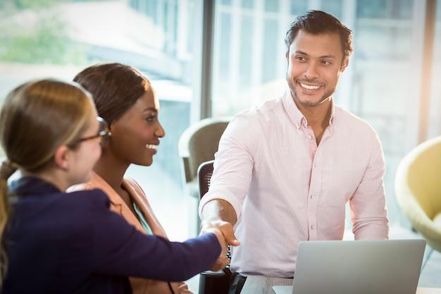 Compañero de trabajo dándose la mano con un colega durante la reunión
