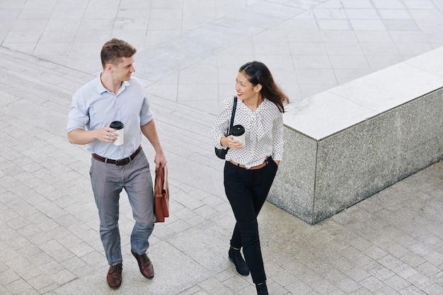 Compañero de trabajo multiétnico bebiendo café para llevar al caminar al edificio de oficinas por la mañana