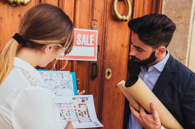Compañero de trabajo observando los planos de la casa