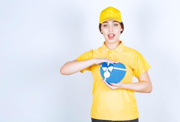 Compañero de trabajo en un unishape amarillo con caja de regalo