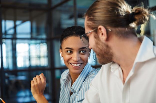 Compañeros alegres multinacionales con auriculares hablando y sonriendo mientras trabaja en la oficina