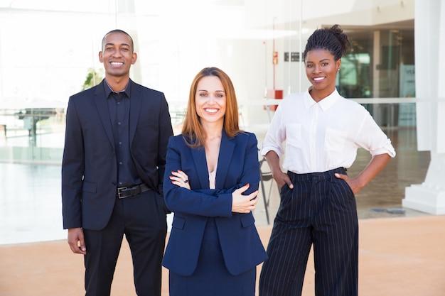 Compañeros alegres de negocios interculturales en trajes formales