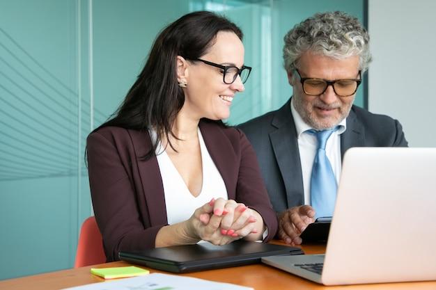 Compañeros alegres o socios de negocios reunidos y discutiendo el proyecto, sentados en el portátil abierto, usando la tableta, hablando y sonriendo.