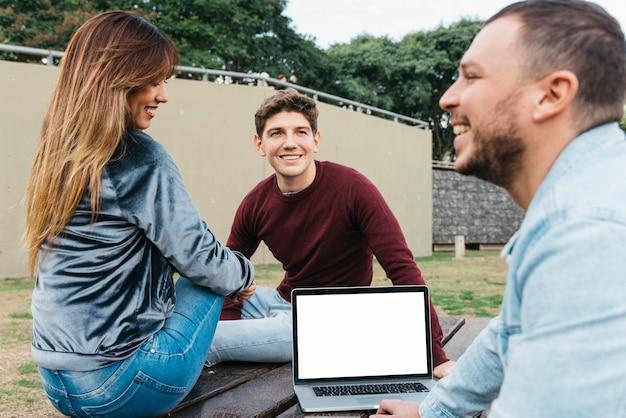 Compañeros alegres que trabajan en la computadora portátil afuera